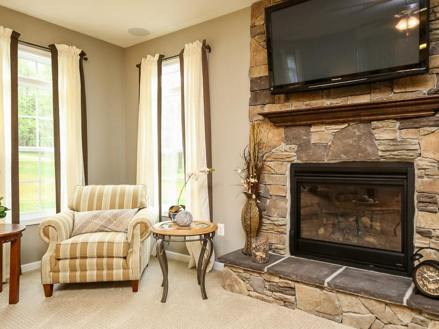 The Chelsey Family Room featuring a Stone Front Fireplace with Stone Box TV Mount.  Cranes Corner Model showing Custom Paint.