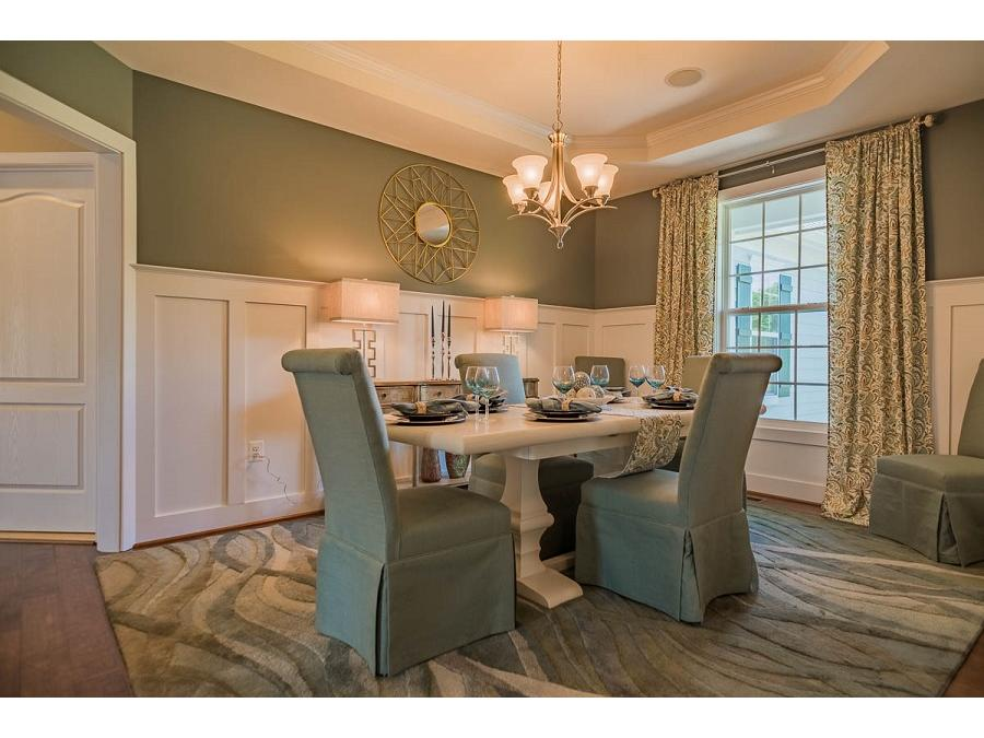 The Bridgewater II Dining Room featuring Custom Wainscot Trim, Tray Ceiling and Hardwood Flooring.