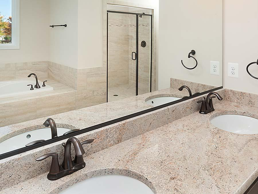 The Montgomery Owner's Bathroom featuring Granite Countertop with Undermount Sinks and Oil Rubbed Faucets