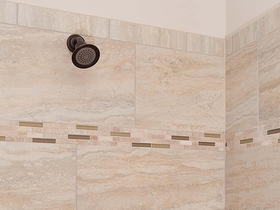 The Montgomery featuring Tier 5  Michelle Crema Vein Cut Tile and Tier 2 Mushroom/ Morning Sun Listello in the Shower