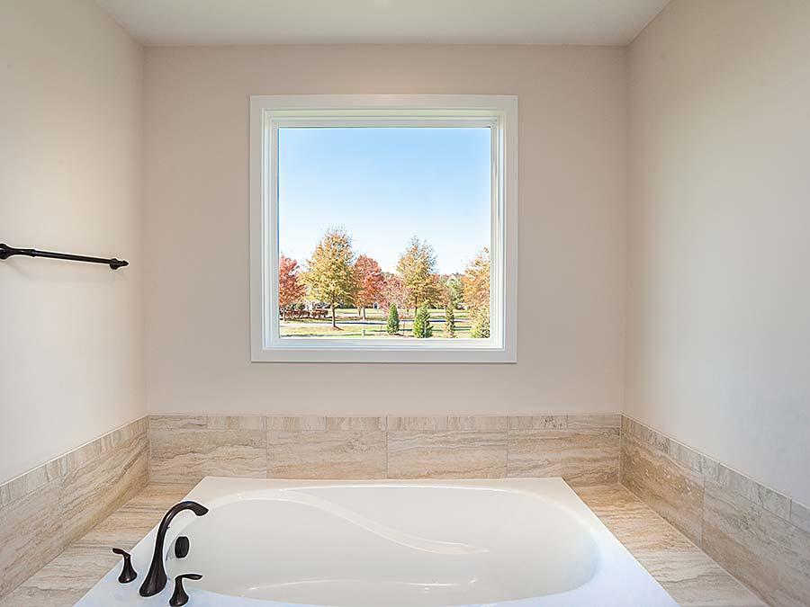 The Montgomery featuring Tier 5  Michelle Crema Vein Cut Tile in the Tub area