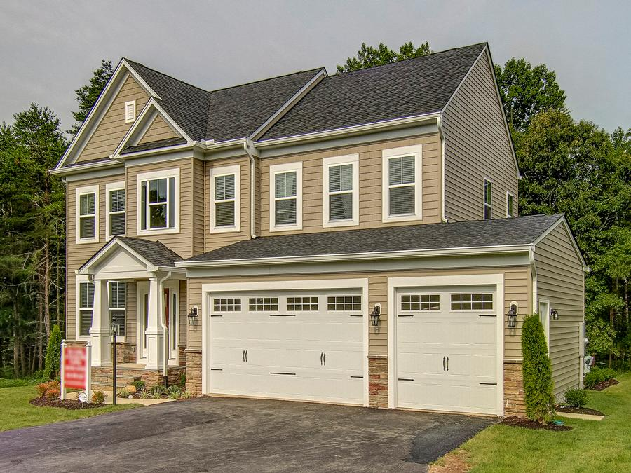 The Griffin Craftsman Elevation featuring 3 Car front load Garage with Carriage Style Doors.