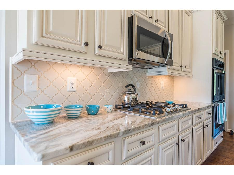 The Bridgewater II Gourmet Kitchen featuring Arabesque Backsplash, Brown Fantasy Granite, Stainless Steel Appliances, and Churchill Maple Painted Ivory with Glaze Cabinets